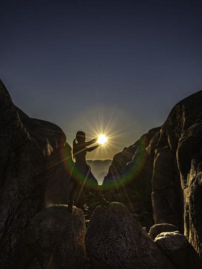 Sun shining over rocks against clear sky