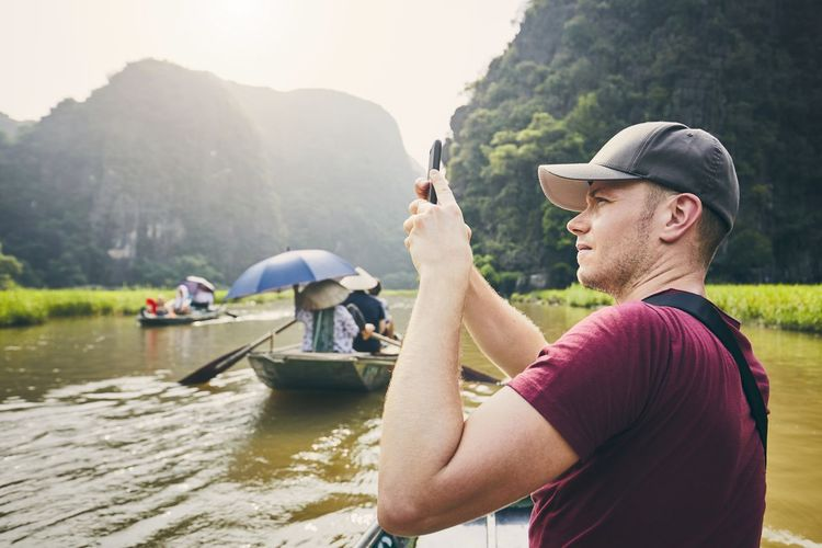 Side view of man photographing in boat against mountains