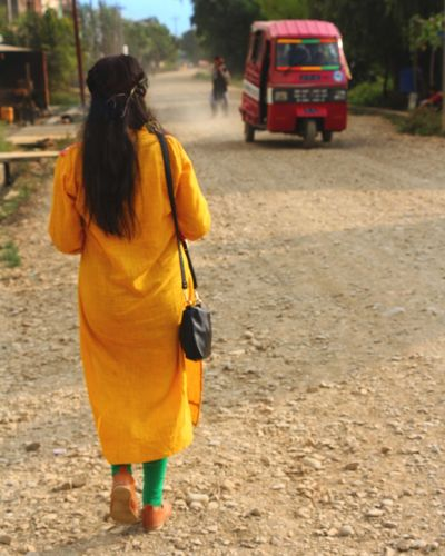 Rear View Full Length Walking Traditional Clothing One Person Adult Black Hair People Only Women One Woman Only Adults Only Women Outdoors Day Young Adult Eyeemnepal Yellow Green Gravel Road Village Road Small Bag Tempo Vehicle Red
