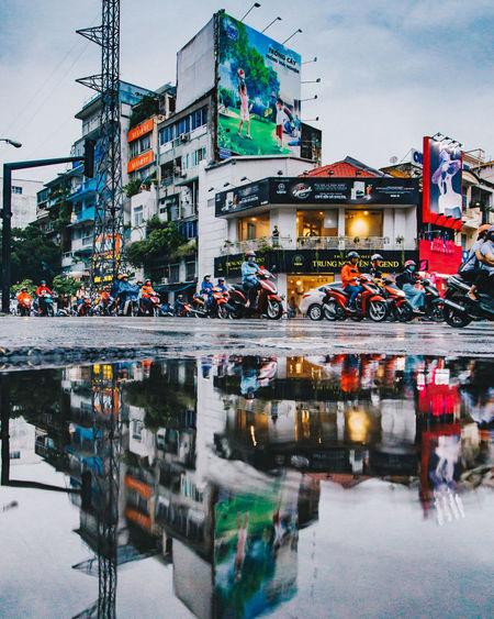 People on street by buildings against sky in city