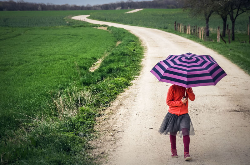 Country Footpath Hided Casual Clothing Day Field Full Length Grass Land Landscape Nature One Person Outdoors Plant Protection Rain Rainy Season Real People Rear View Road Security Umbrella Walking Women