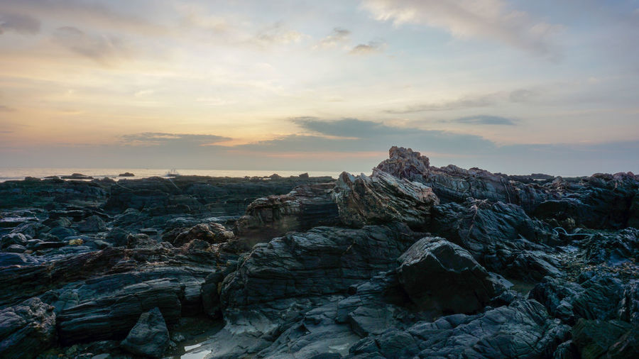Rock formations in sea against sky during sunset