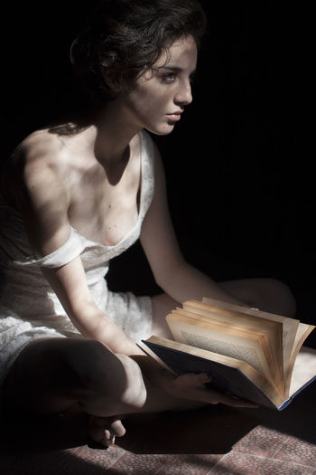 High angle view of beautiful fashion model sitting with book