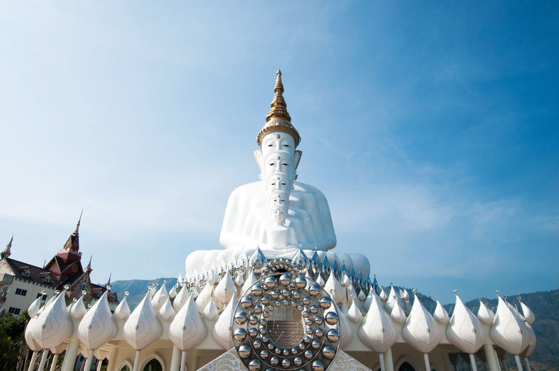 Low angle view of buddha statues at wat pha son kaew against sky