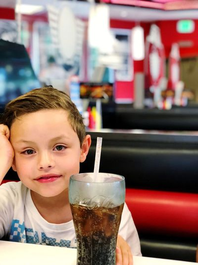 Portrait of smiling boy drinking glass at restaurant