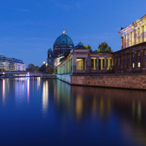 Illuminated bridge by berlin cathedral over river at dusk