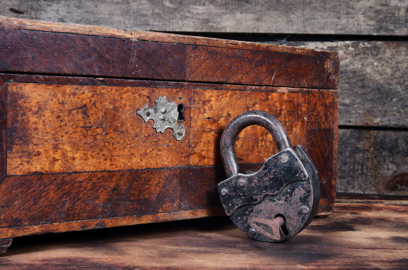 Close-up of old rusty padlock and treasure box on table