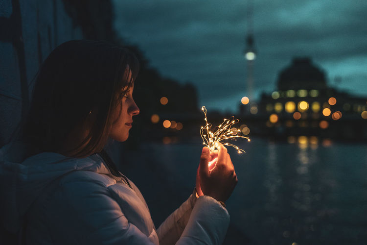 Young woman holding illuminated string light by river at night