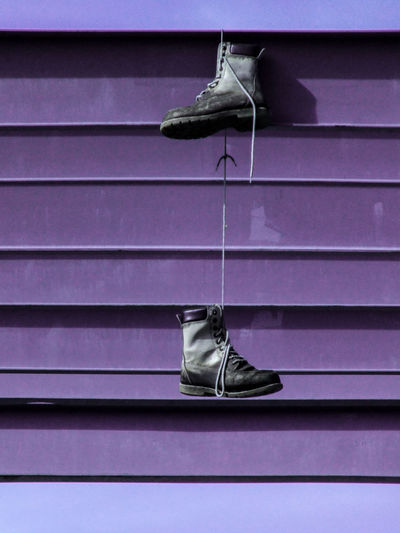 Abandoned shoes hanging on purple metal