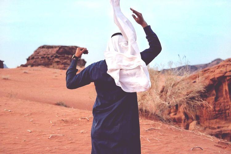 Rear view of man walking in desert against sky