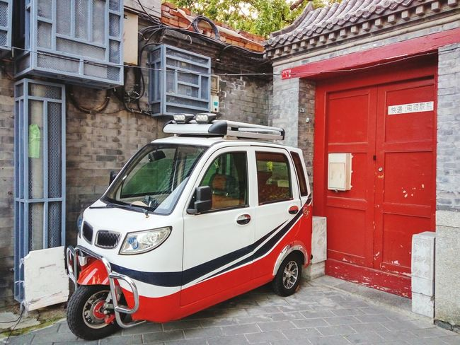 Chinese Small Vehicle Small Car City Car Chinese City Car Red Door Red Garage Door Transportation Red Outdoors Building Exterior Architecture Mode Of Transport Built Structure No People Land Vehicle Day
