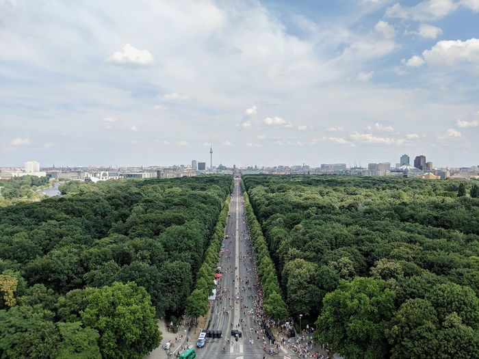 Aerial view of trees in city against cloudy sky