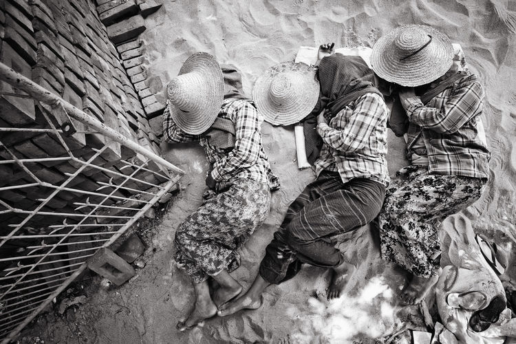 High angle view of female workers relaxing on sand at construction site