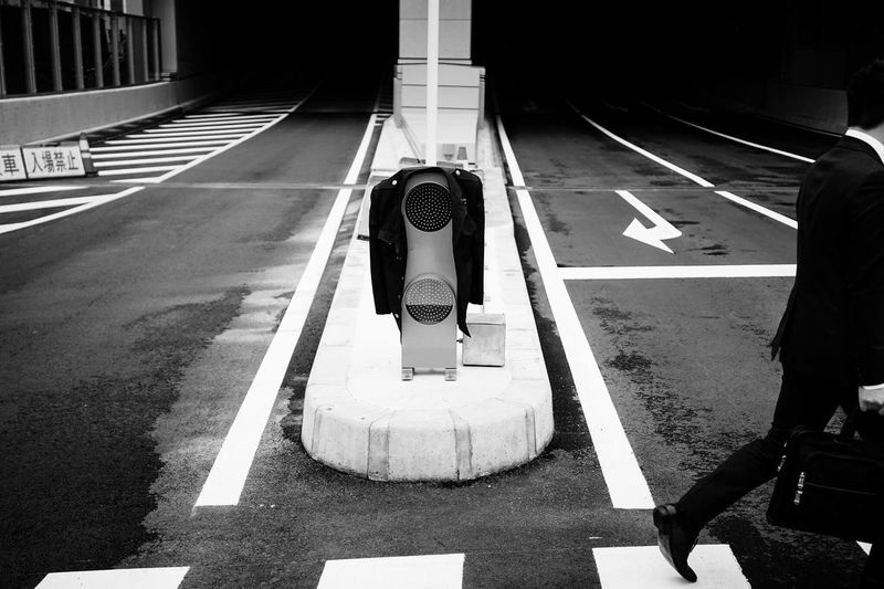 Rear view of man walking by road signal on street
