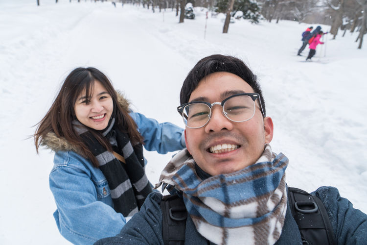 E M ASIA Asian  Couple Japan Japan Photography Japanese  Travel Clothing Cold Temperature Couple - Relationship Day Emotion Front View Happiness Leisure Activity Looking At Camera Outdoors People Portrait Real People Sapporo Smiling Snow Snowing Togetherness Two People Warm Clothing White Color Winter Women Young Adult