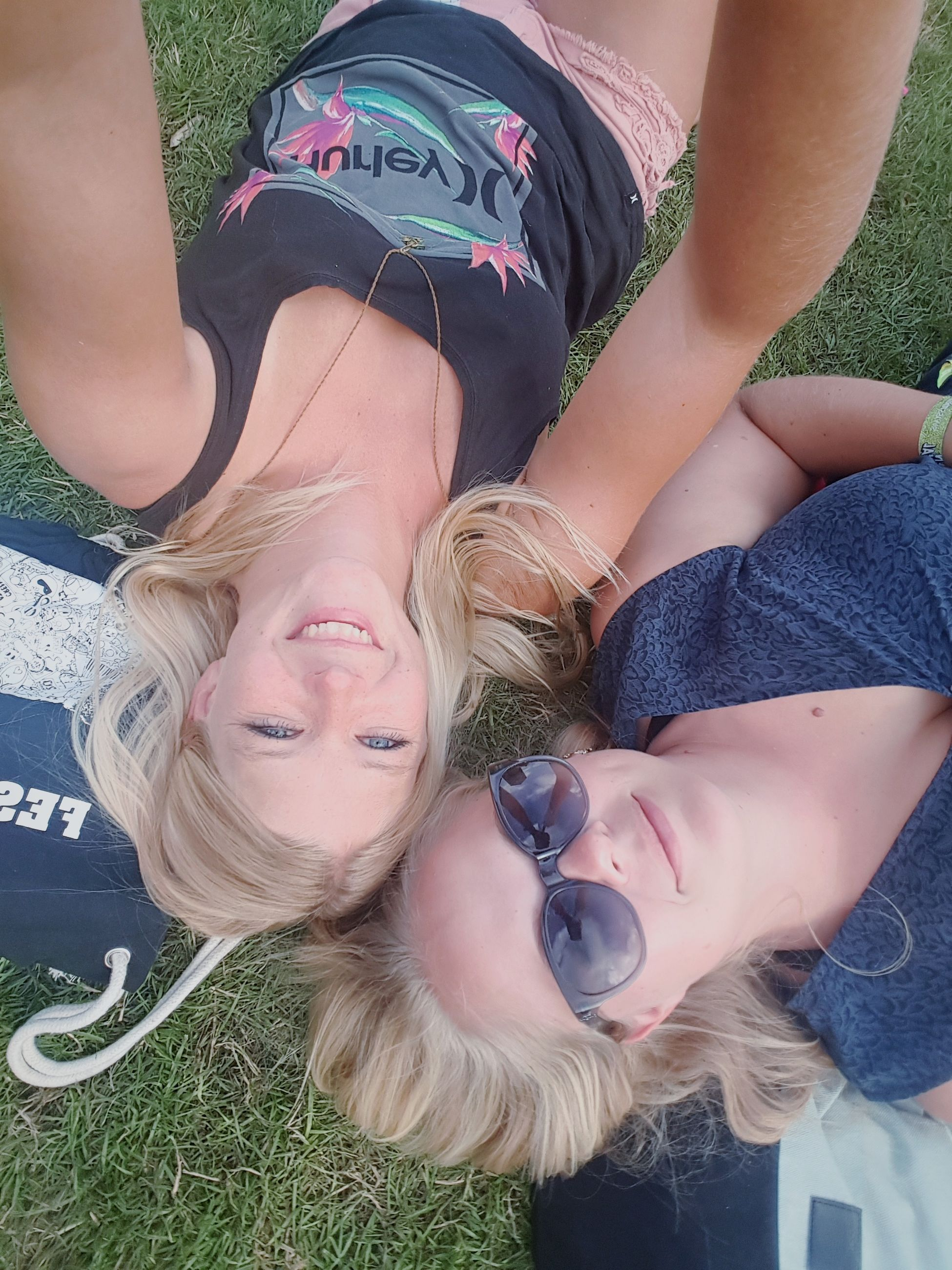 real people, leisure activity, childhood, togetherness, casual clothing, lifestyles, girls, happiness, high angle view, smiling, lying down, lying on back, elementary age, day, mother, outdoors, love, bonding, sibling, two people, looking at camera, young women, grass, portrait, boys, young adult, blond hair, close-up