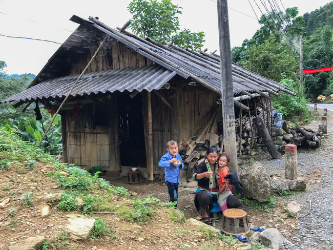 family in village in Sapa ,north vietnam Family Architecture Boys Building Exterior Built Structure Casual Clothing Childhood Day Full Length Girls Leisure Activity Lifestyles Men Nature Outdoors People Portrait Real People Sky Standing Togetherness Tree Young Adult
