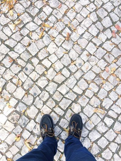 Low section of man wearing shoes standing on cobbled street during autumn
