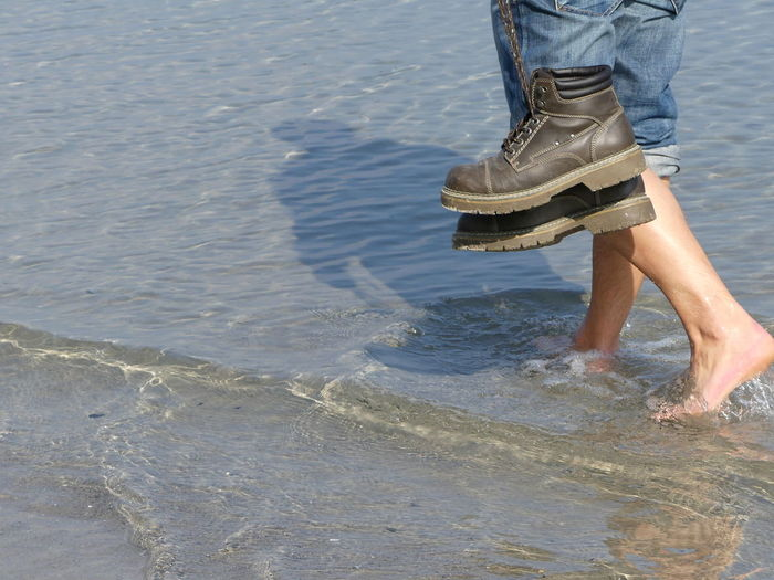Low section view of man walking in water on beach