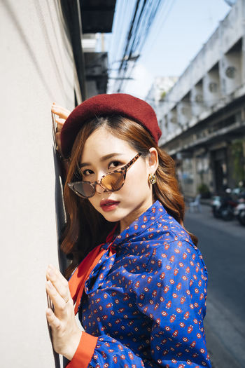 Portrait of young woman wearing sunglasses against wall outdoors