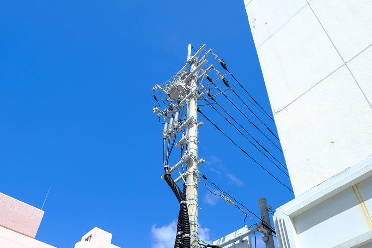 Low Angle View Of Telephone Lines Amidst Buildings Against Blue Sky