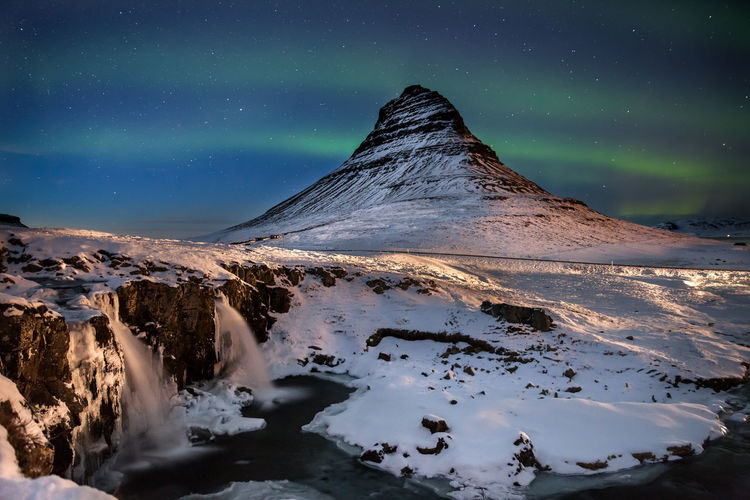Scenic view of snowcapped mountain against sky during aurora borealis