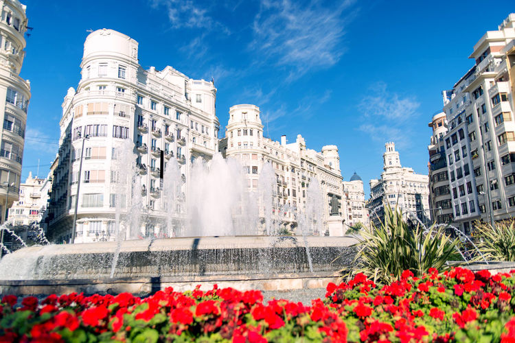 Valencia square with a fountain and flowers Architecture Building Exterior Flower Built Structure Flowering Plant Plant Nature City Day Sky Water Low Angle View Building Fountain Outdoors Freshness Travel Destinations No People Growth Flowerbed Spraying Valencia, Spain