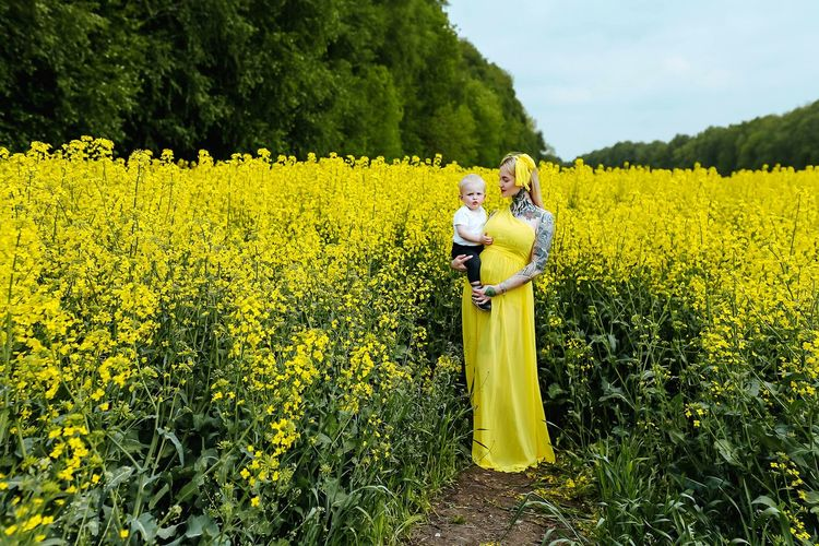 Pregnant woman with daughter standing by plants