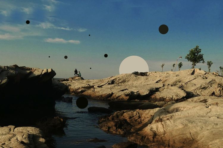 Hot air balloons flying over rocks against sky