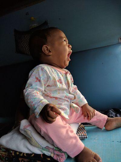 Cute baby girl yawning while looking away in train