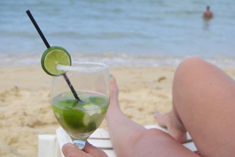 Low section of woman holding lemonade glass while relaxing at beach