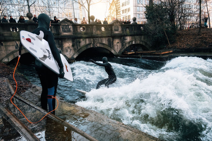 The surfer in diving suit wait their turn to ride the artificial wave on the Eisbach, dangerous water Isar river channel at Englischer Garden, Munich, Germany Munich Riverside Surf Wave Activity Bridge - Man Made Structure Built Structure City Motion Outdoors People Real People River Sport Surfing Surfingphotography Water Go Higher Focus On The Story