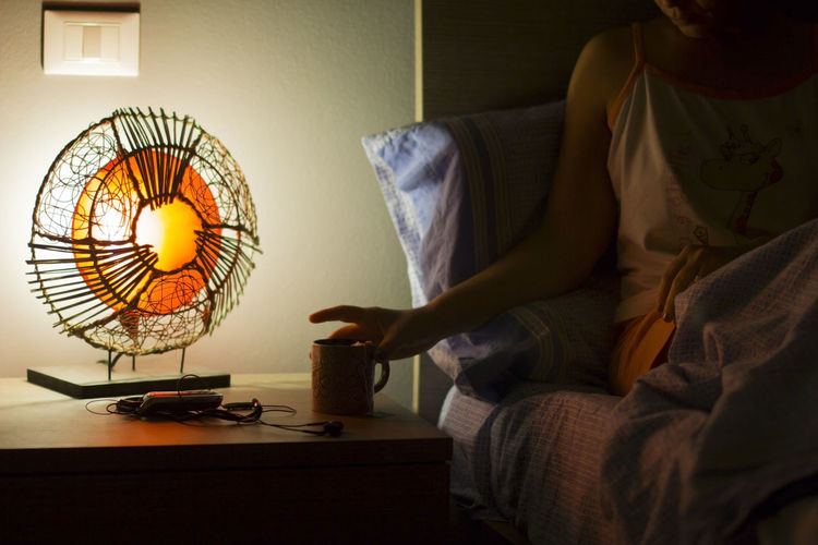 Midsection of woman with mug sitting on bed