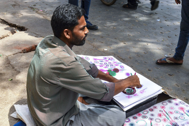 High angle view of man sitting on street