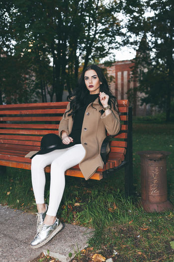 Portrait of beautiful woman sitting on bench at public park