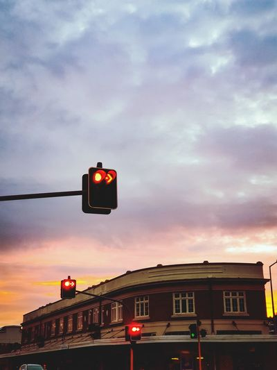 Low angle view of road signal against sky during sunset