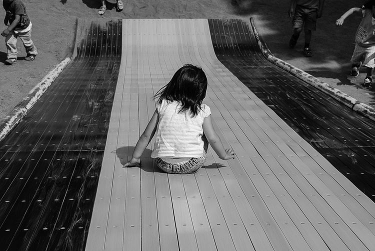 Rear View Of Girl Playing On Slide During Sunny Day