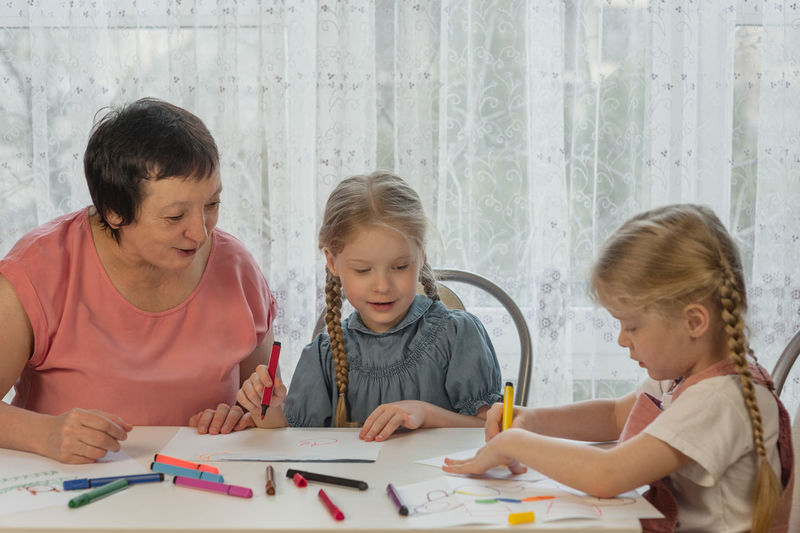 Grandmother sitting with granddaughters during painting