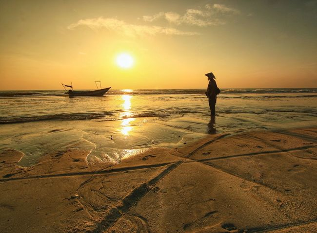 A fisherman looking the boat at the beach with nice sunrise Water Full Length Sea Sunset Beach Standing Sand Sunlight Silhouette Summer Low Tide Fishing Boat Fisherman Boat Sun Shining Tide