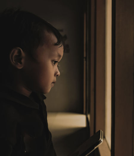 Close-up portrait of boy looking away at home