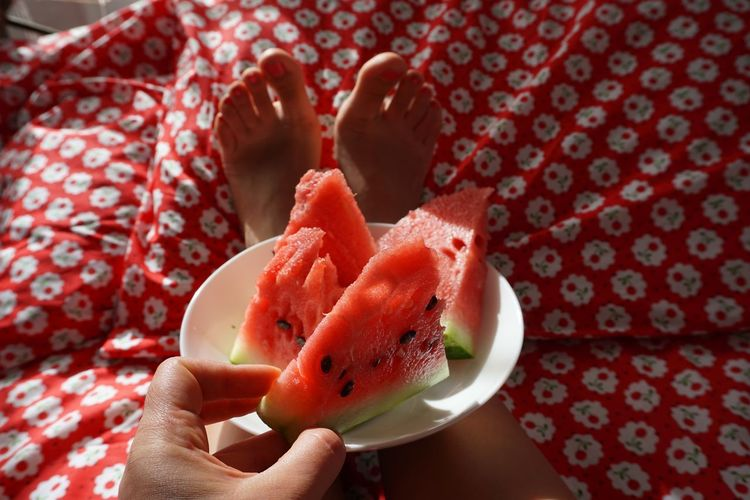 Low section of woman with watermelon slices on bed