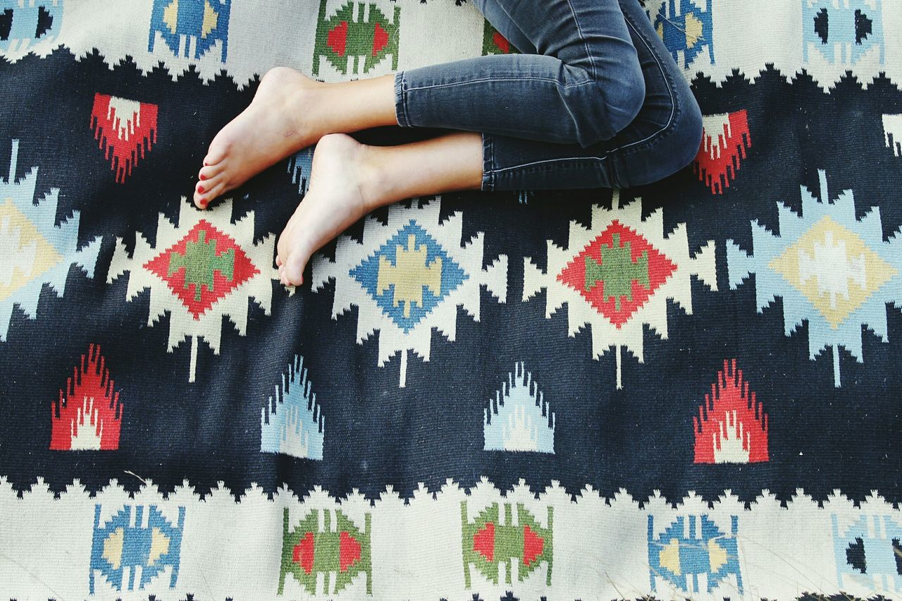 Low section of woman lying on carpet