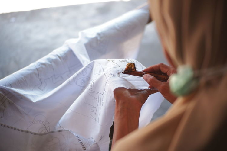 Midsection of woman making batik painting