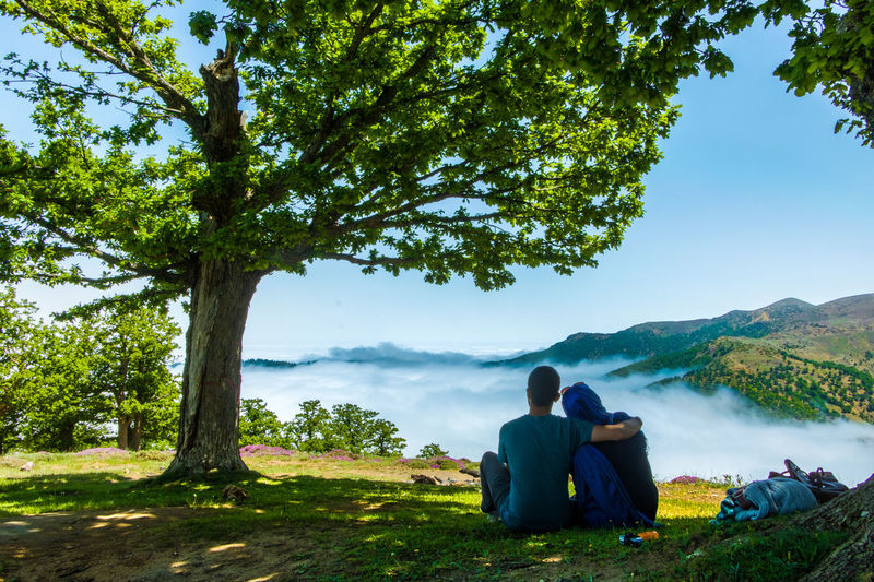 Rear view of couple sitting on mountain against sky