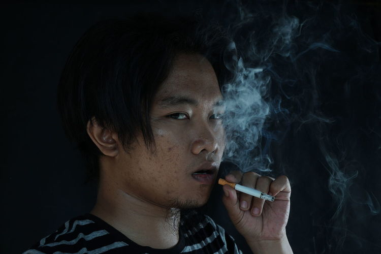 Portrait of a man smoking cigarette isolated on black background. Addiction Adult Bad Habit Black Background Cigarette  Close-up Headshot Indoors  Lifestyles Marijuana - Herbal Cannabis Night One Person People Real People RISK Smoke - Physical Structure Smoking - Activity Smoking Issues Social Issues Studio Shot Young Adult