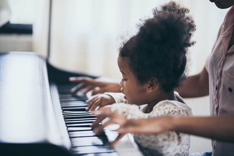 Midsection of woman playing piano with daughter