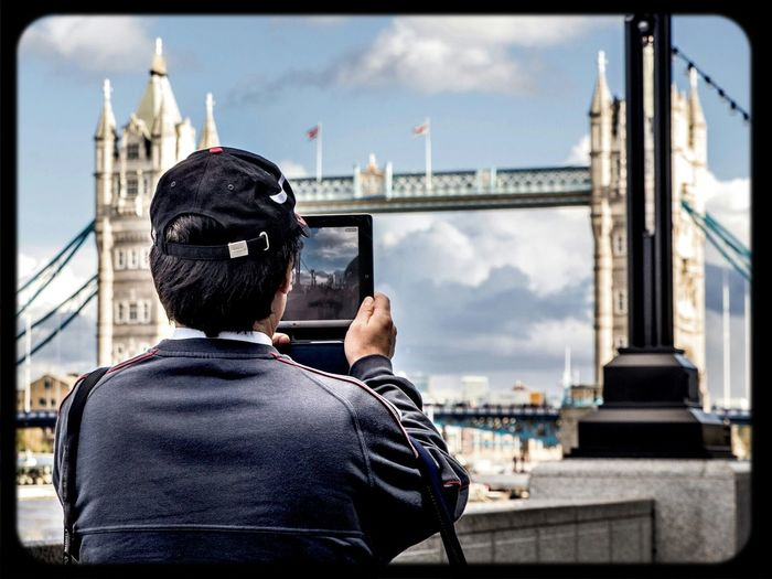 Man photographing tower bridge with tablet