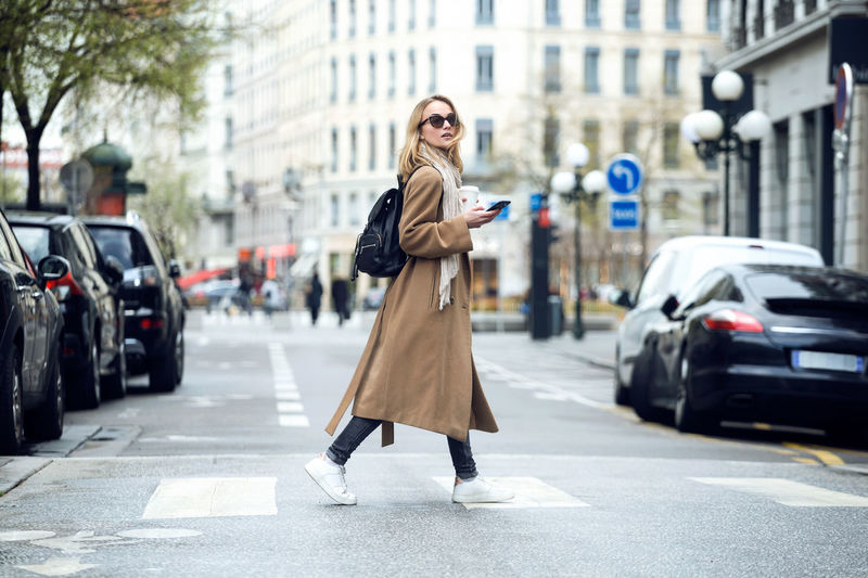 Woman with coffee cup using mobile phone on city street