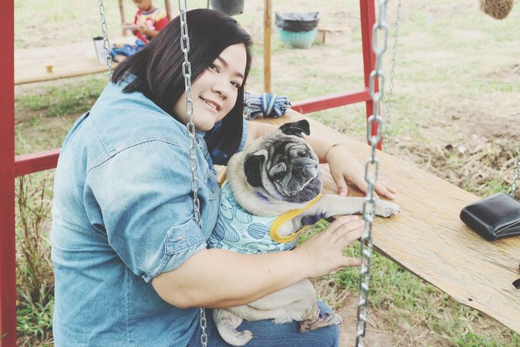 Portrait of woman with dog sitting on swing
