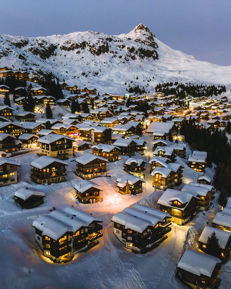 High angle view of snow covered houses and buildings in city